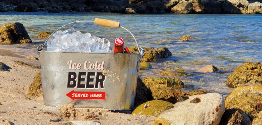 A beer bucket cooling down on the beach